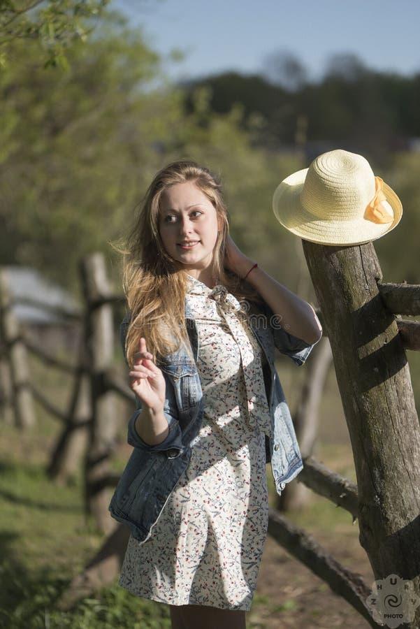 Piękna dziewczyna stoi w naturze blisko drewnianego ogrodzenia obraz royalty free