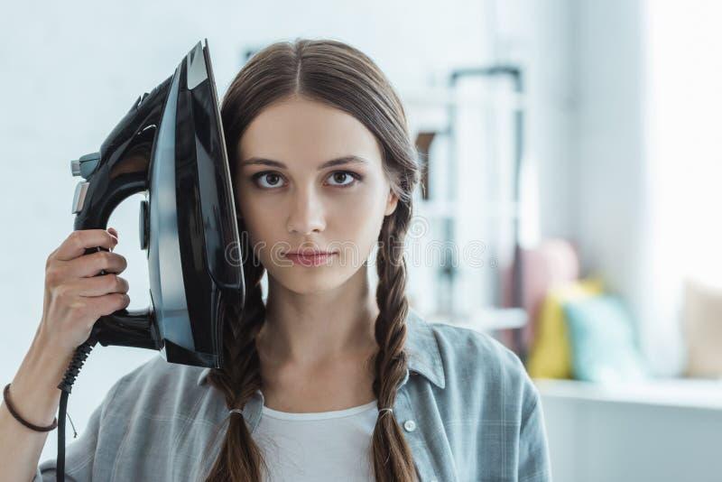 piękna dziewczyna trzyma żelazo z warkoczami obraz stock