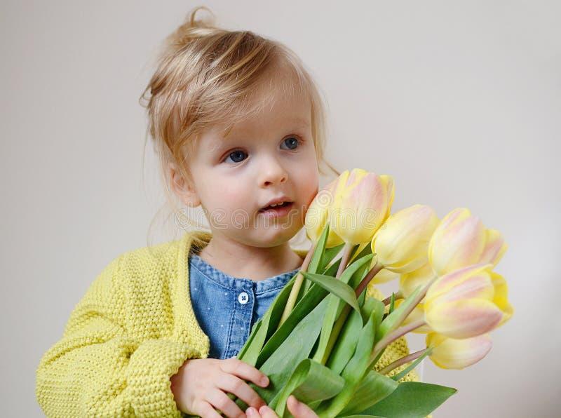 Piękna dziewczyna trzyma bukiet żółci tulipany zdjęcia stock