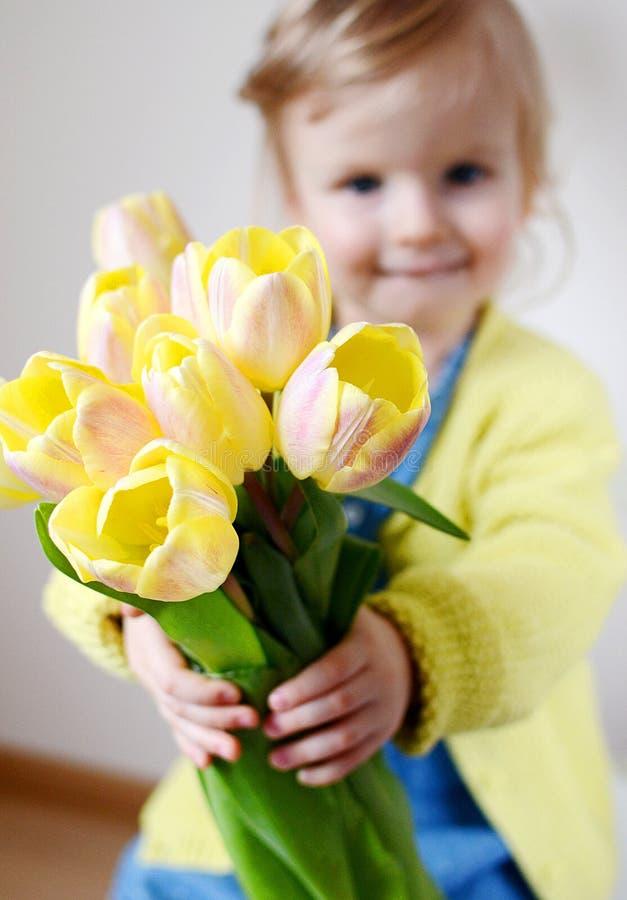 Piękna dziewczyna trzyma bukiet żółci tulipany obrazy stock
