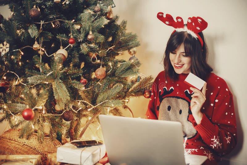 Piękna dziewczyna trzyma kredytową kartę i shopp w reniferowych poroże fotografia stock