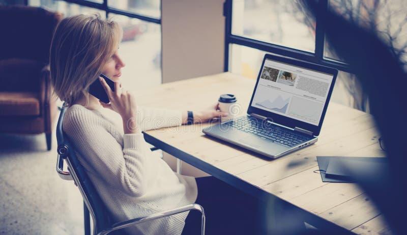 Piękna dziewczyna używa laptop i smartphone przy drewnianym stołem w coworking studiu Pojęcie młodzi ludzie pracuje z obraz stock