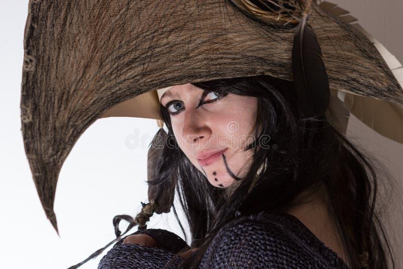 Piękna dziewczyna ubierał w kostiumu z czerni piórkami i wrony głowie na białym tle czarownicy lub szamanu obraz stock