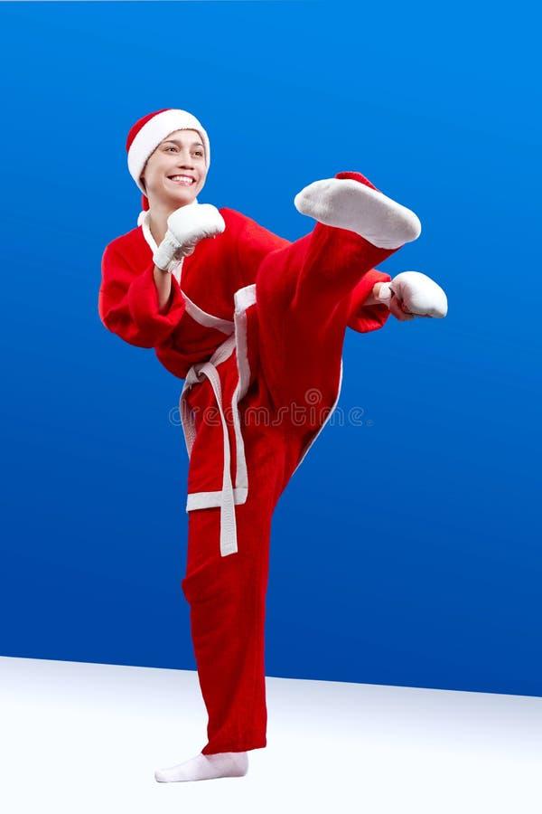 Piękna dziewczyna ubierająca jako Santa robi karate kopnięcia lewej stopie zdjęcie royalty free