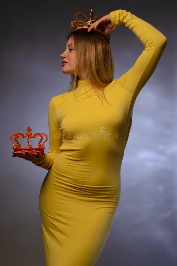 Piękna dziewczyna w żółtej wieczór sukni trzyma jeden koronę w jego brzęczeniach zdjęcie royalty free