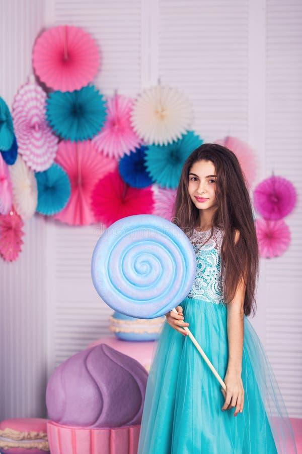 Piękna dziewczyna w błękit sukni chwycie w ręka ogromnym cukierku w studiu z wystrojem macaroons kosmos kopii obraz stock