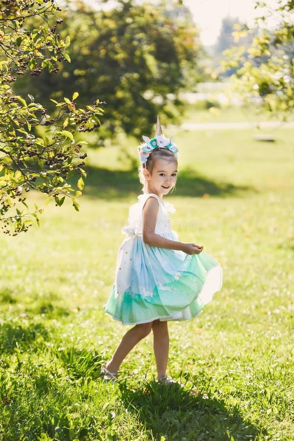 Piękna dziewczyna w błękitnej sukni w zielonego ogródu parka uśmiechniętym słonecznym dniu świętuje Halloween z jednorożec obrazy stock