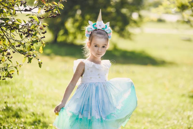 Piękna dziewczyna w błękitnej sukni w zielonego ogródu parka uśmiechniętym słonecznym dniu świętuje Halloween z jednorożec fotografia royalty free