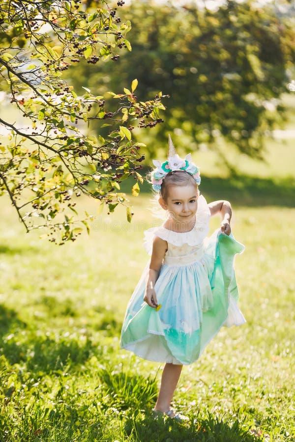 Piękna dziewczyna w błękitnej sukni w zielonego ogródu parka uśmiechniętym słonecznym dniu świętuje Halloween z jednorożec obrazy royalty free