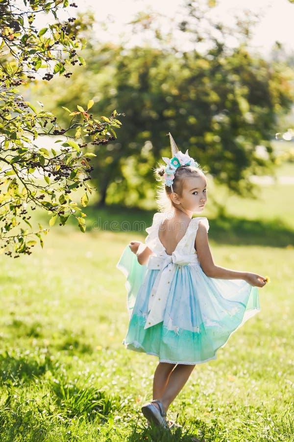 Piękna dziewczyna w błękitnej sukni w zielonego ogródu parka uśmiechniętym słonecznym dniu świętuje Halloween z jednorożec fotografia stock