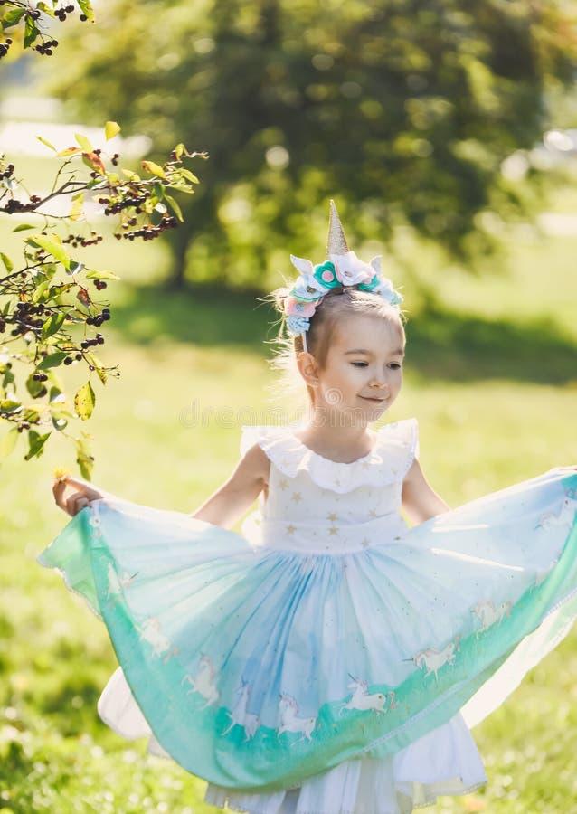 Piękna dziewczyna w błękitnej sukni w zielonego ogródu parka uśmiechniętym słonecznym dniu świętuje Halloween z jednorożec obraz stock
