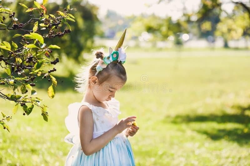 Piękna dziewczyna w błękitnej sukni w zielonego ogródu parka uśmiechniętym słonecznym dniu świętuje Halloween z jednorożec zdjęcia stock