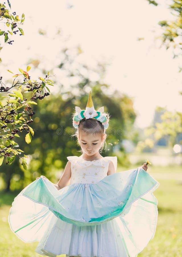 Piękna dziewczyna w błękitnej sukni w zielonego ogródu parka uśmiechniętym słonecznym dniu świętuje Halloween z jednorożec zdjęcie stock