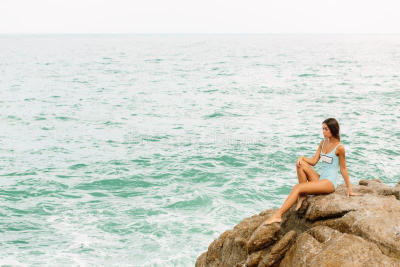 Piękna dziewczyna w błękitnym swimsuit siedzi na dużym kamieniu obrazy stock