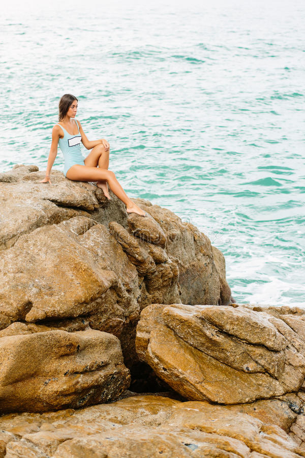 Piękna dziewczyna w błękitnym swimsuit siedzi na dużym kamieniu obraz royalty free