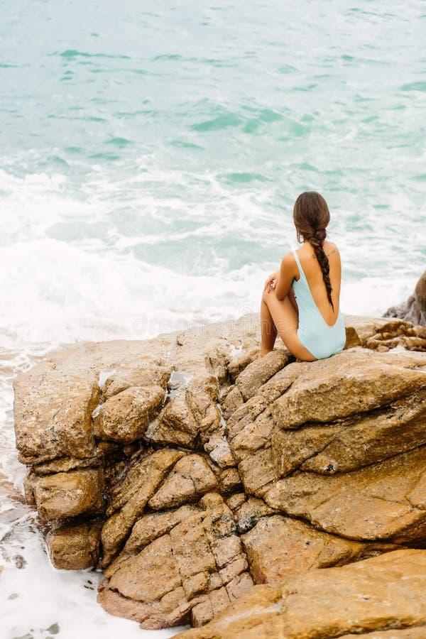 Piękna dziewczyna w błękitnym swimsuit siedzi na dużym kamieniu obraz stock