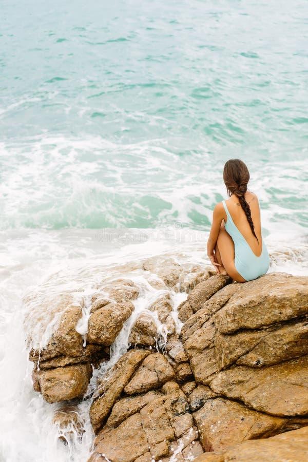 Piękna dziewczyna w błękitnym swimsuit siedzi na dużym kamieniu zdjęcia royalty free