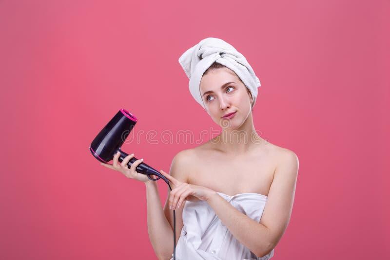 Piękna dziewczyna w białym ręczniku na głowie, chwytach i spojrzeniach przy stann jej, włosiana suszarka obrazy royalty free