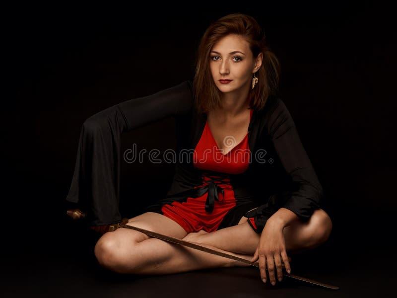 Piękna dziewczyna w czerwonej sukni z ośniedziałym meme na jej kolanie obraz royalty free