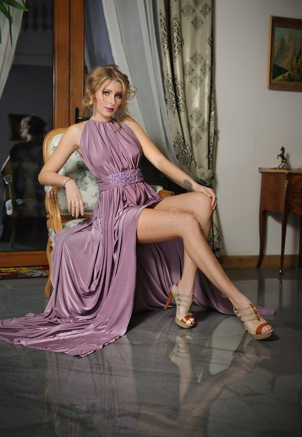 Piękna dziewczyna w długich menchii smokingowy pozować w rocznik scenerii Młoda wspaniała kobieta jest ubranym eleganckiej sukni  obrazy royalty free