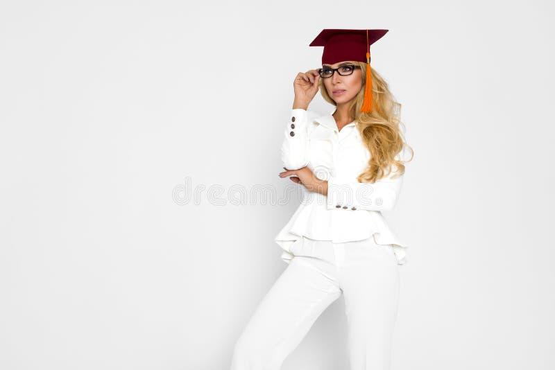 Piękna dziewczyna w gratuate stroju stoi na białym tle w studiu w salopie, Jest absolwentem obraz royalty free