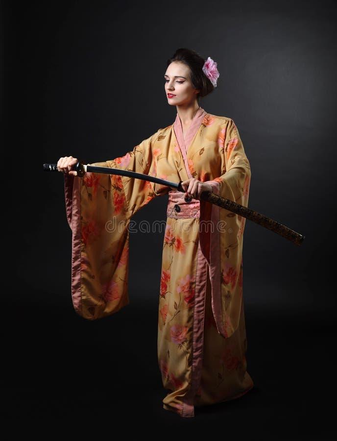 Piękna dziewczyna w kimonie z japońskim kordzika kataną na czerni zdjęcie royalty free
