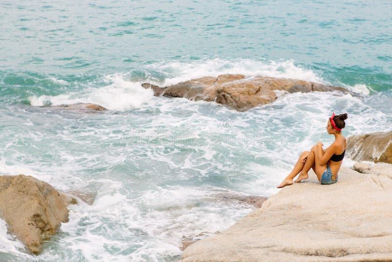 Piękna dziewczyna w krótkich skrótach siedzi na dużych kamieniach zdjęcia stock