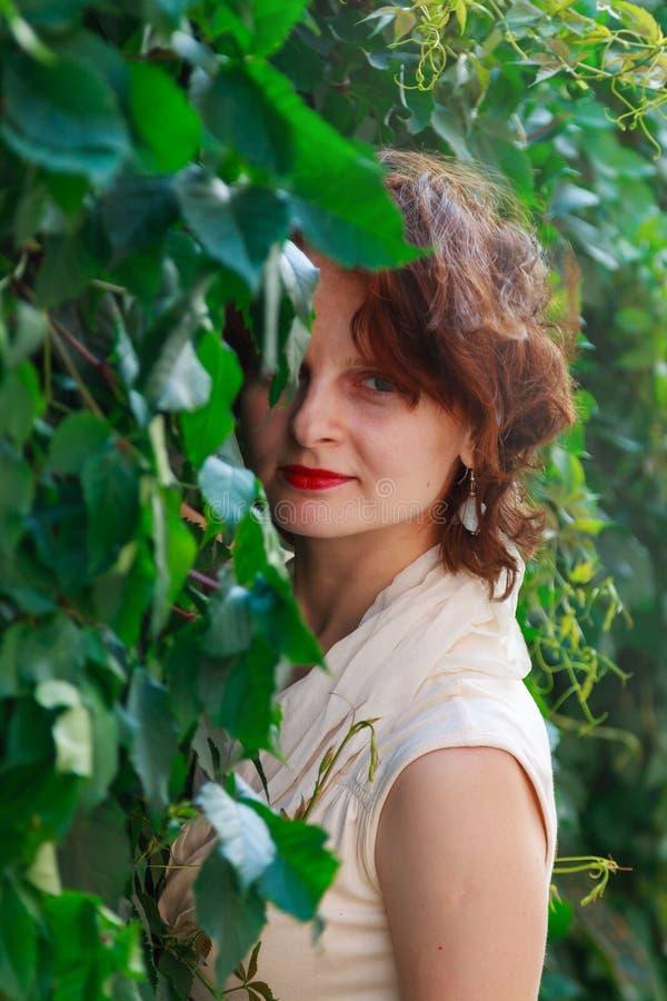Piękna dziewczyna w lekkiej beż sukni w zielonych liściach zdjęcia stock