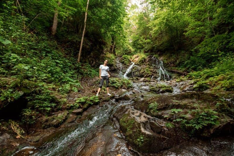 Piękna dziewczyna w małym wodospadzie, karpacki strumień górski. Koncepcja podróży, rekreacja, wakacje fotografia stock