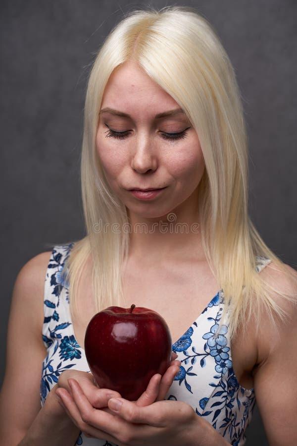 Piękna dziewczyna w modnej sukni z jabłkiem obraz stock