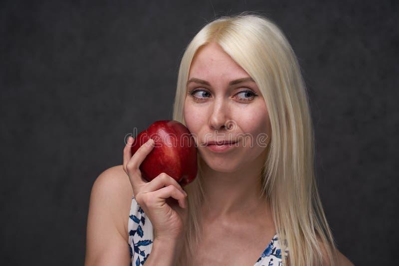 Piękna dziewczyna w modnej sukni z jabłkiem obrazy royalty free