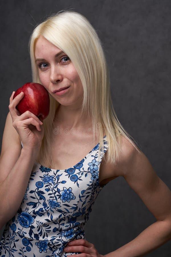 Piękna dziewczyna w modnej sukni z jabłkiem zdjęcie stock