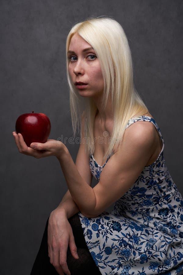 Piękna dziewczyna w modnej sukni z jabłkiem obrazy stock