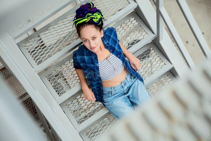 Piękna dziewczyna w przypadkowych ubraniach cajgi i szkockiej kraty koszula z colourful dreadlocks, zdjęcie stock