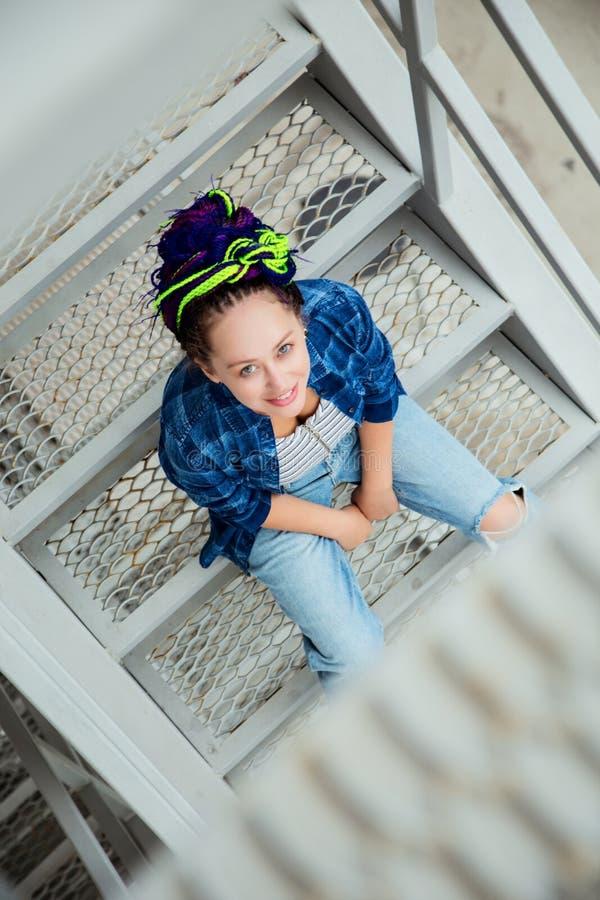 Piękna dziewczyna w przypadkowych ubraniach cajgi i szkockiej kraty koszula z colourful dreadlocks, obrazy stock