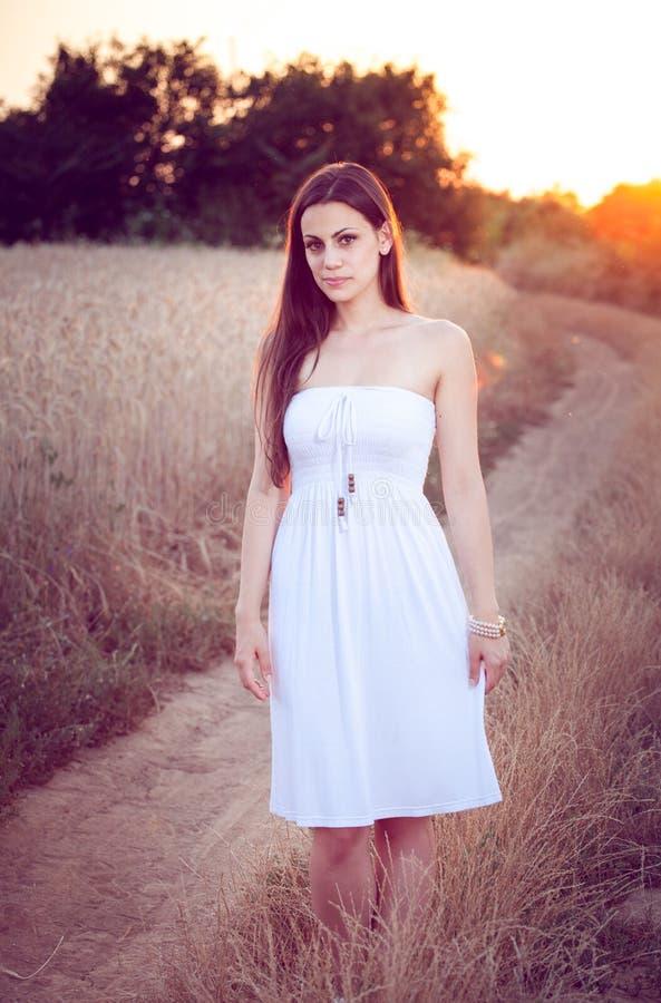 Piękna dziewczyna w pszenicznym polu przy zmierzchem obraz stock