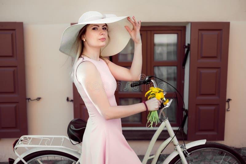 Piękna dziewczyna w różowej sukni z kwiatami na bicyklu Portret obrazy stock