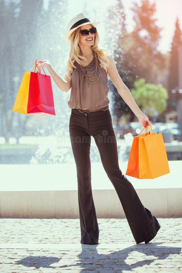 Piękna dziewczyna w słońc szkłach trzyma torba na zakupy i ono uśmiecha się obrazy royalty free