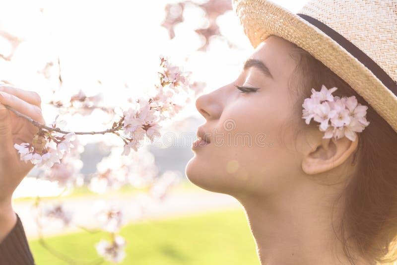 Piękna dziewczyna w słomianym kapeluszu obwąchuje okwitnięcie gałąź obraz stock