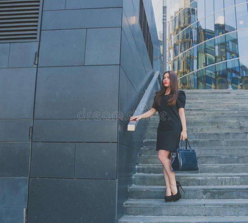 Piękna dziewczyna w smokingowym nadchodzącym puszku kroki od centrum biznesu fotografia stock