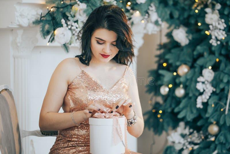 Piękna dziewczyna w smokingowym obsiadaniu blisko odpakowania i choinki prezent fotografia stock