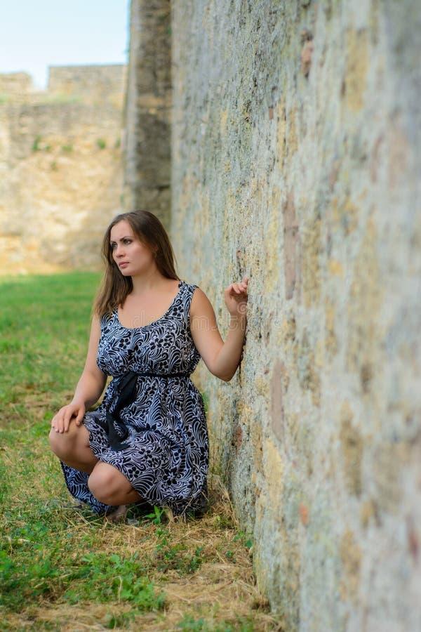Piękna dziewczyna w smokingowym obsiadaniu na tle forteczna ściana fotografia stock