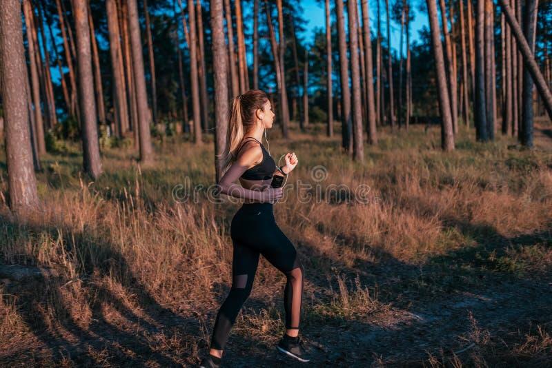 Piękna dziewczyna w sportswear bieg na bieg Kobieta słucha muzyka w lecie w lesie Z hełmofonami fotografia royalty free