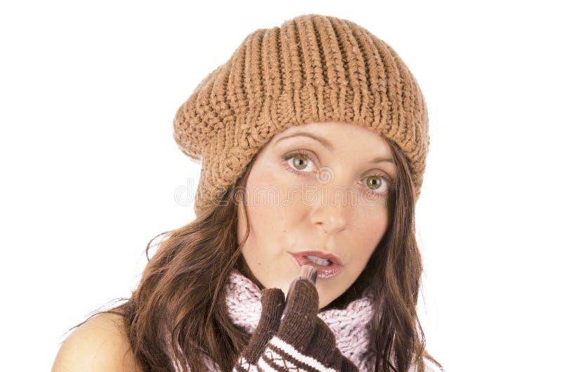 Piękna dziewczyna w zimie odziewa, stawiający pomadkę obraz stock