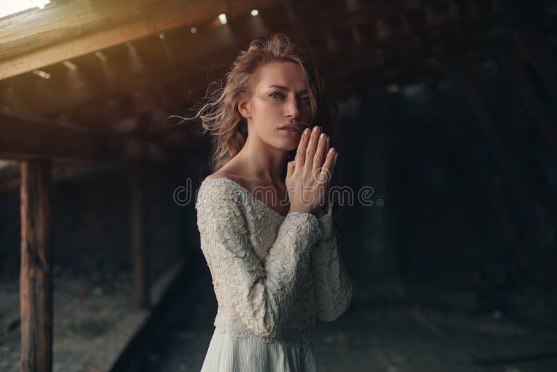 Piękna dziewczyna wewnątrz w białej rocznik sukni z kędzierzawym włosy pozuje na attyku retro smokingowa kobieta Zmartwiona zmysł obraz royalty free