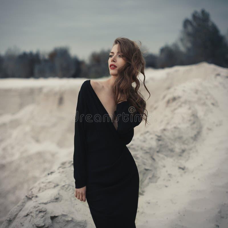 Piękna dziewczyna wewnątrz w czarnej rocznik sukni z kędzierzawym włosy pozuje na piasku Kobieta w retro dresach Zmartwiona zmysł obraz stock