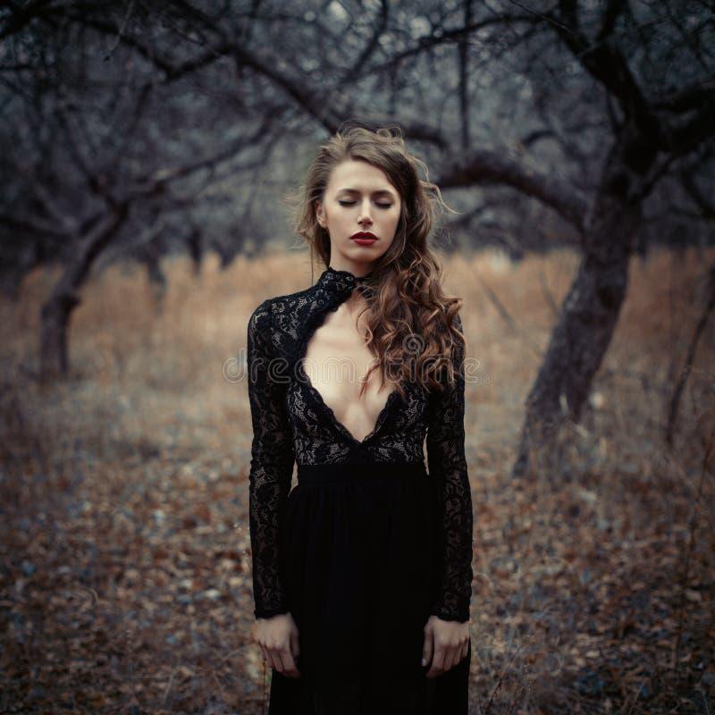 Piękna dziewczyna wewnątrz w czarnej rocznik sukni z kędzierzawym włosy pozuje w drewnach Kobieta w retro sukni gubjącej w lasowy zdjęcia stock