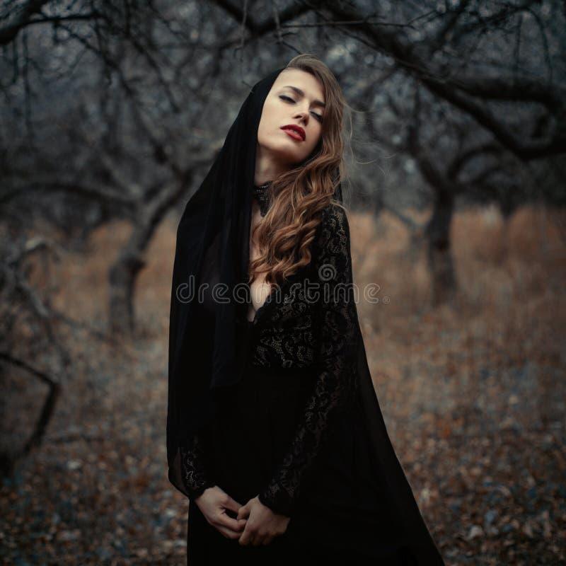 Piękna dziewczyna wewnątrz w czarnej rocznik sukni z kędzierzawym włosy pozuje w drewnach Kobieta w retro sukni gubjącej w lasowy obrazy royalty free