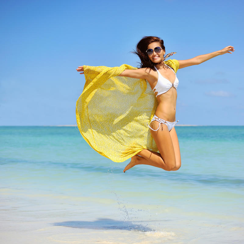Piękna dziewczyna z żółtym szalika doskakiwaniem na plaży Podróżuje zdjęcie royalty free