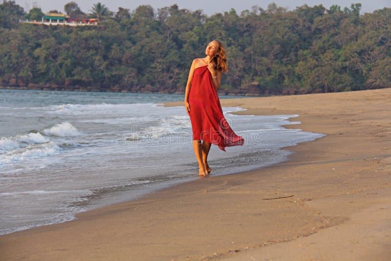 Piękna dziewczyna z blondynem, w czerwonej sukni, chodzi wzdłuż th fotografia royalty free